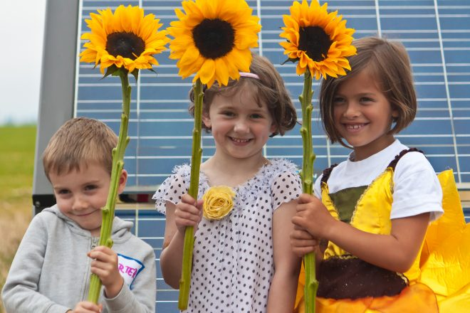 3 children with sunflowers in front of solar panels