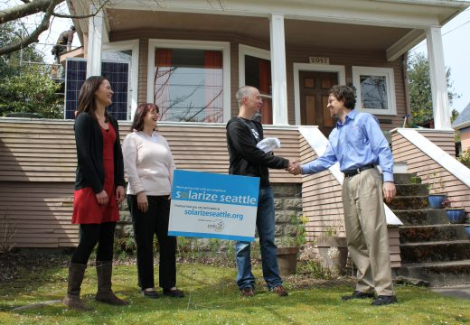 Four happy people standing in front yard with Solarize Seattle sign at Solarize Queen Anne