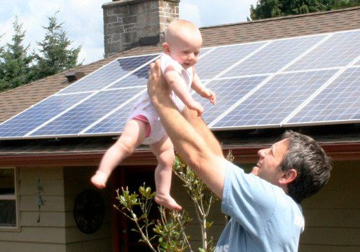 father holding baby with solar panels in background