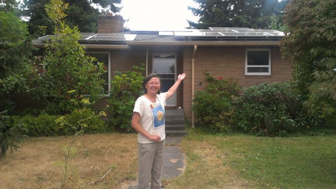 Pamela Ng standing in front of solar panels installed on her roof
