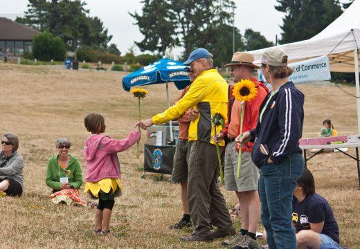 Volunteer holding sunflowers at Solarize Seattle: Northwest