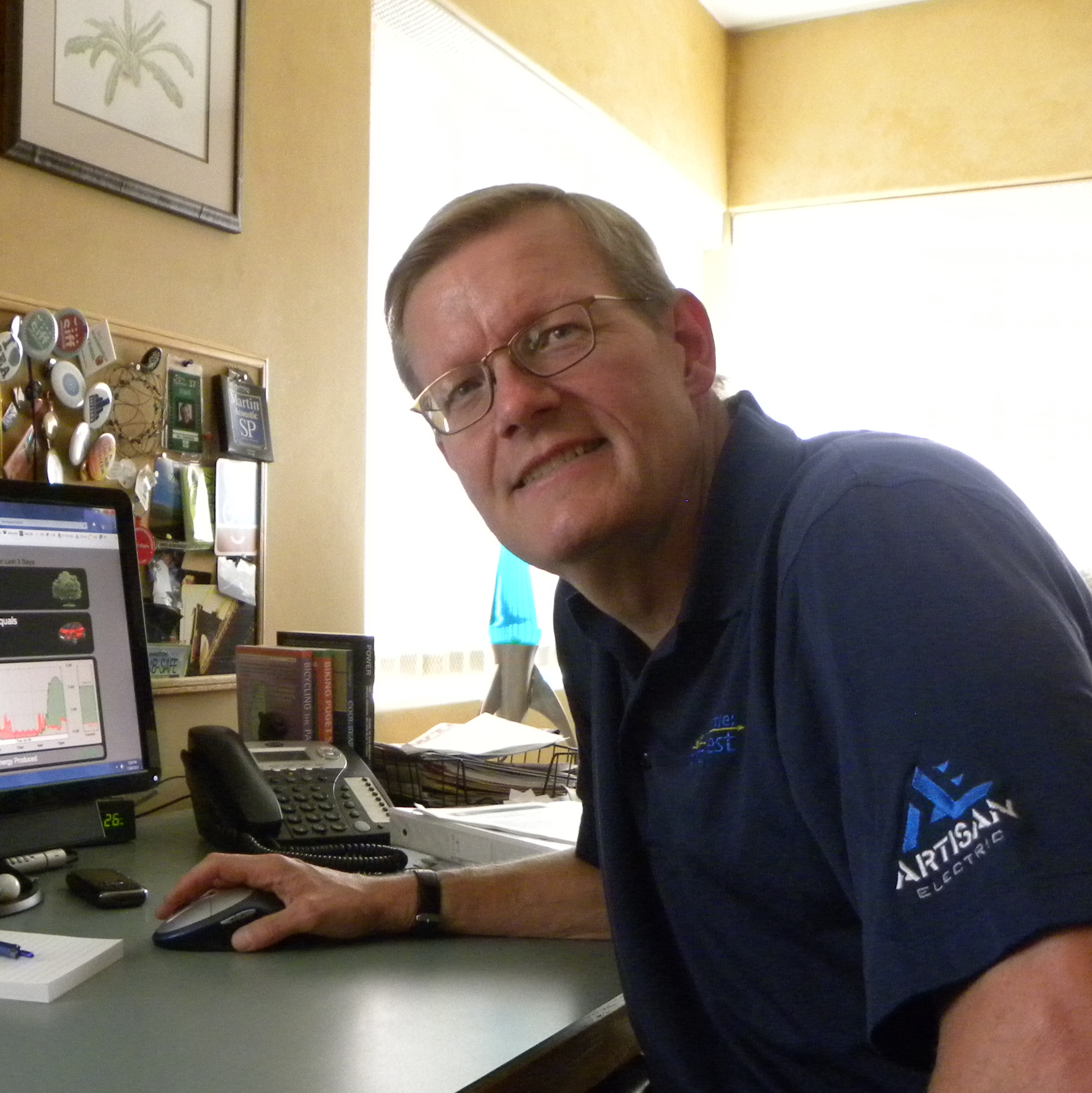 Bill Thorness sitting at his desk with EGauge reading