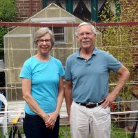 Bruce and Mary standing in front of their home