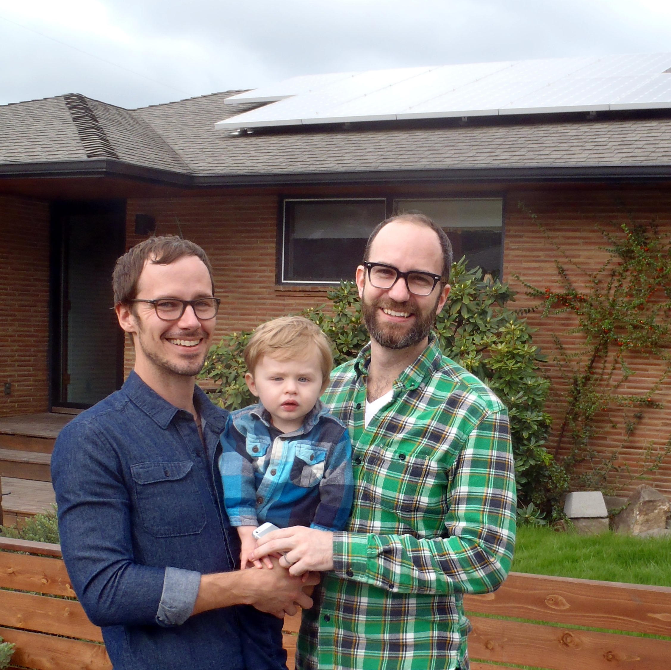 Stephen and Dooley with child standing in front of their home