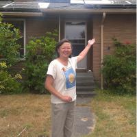 Pamela Ng in front of solar panels