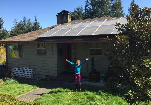 Girl standing in front of home with solar panels